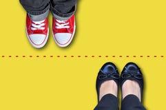 Ligne rouge qui sépare des espadrilles et des chaussures classiques Images libres de droits