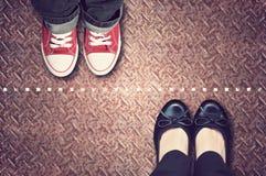 Ligne rouge qui sépare des espadrilles et des chaussures classiques Image libre de droits