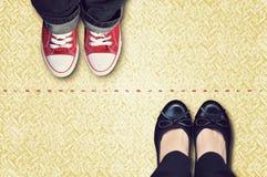 Ligne rouge qui sépare des espadrilles et des chaussures classiques Photo stock
