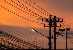 Ligne téléphonique de courrier et de lampe avec un coucher du soleil de fond sur la rue Photographie stock
