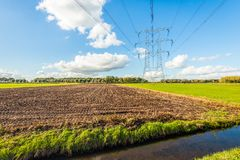 Lignes à haute tension et pylônes de puissance dans un paysage rural images stock