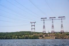 Lignes à haute tension rouges sur une île pierreuse contre un ciel bleu Photographie stock