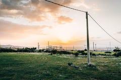 Lignes électriques électriques au coucher du soleil Images stock