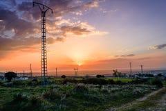 Lignes électriques électriques au coucher du soleil Photographie stock libre de droits