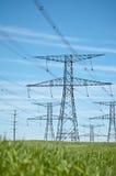 Lignes électriques avec le ciel bleu et l'herbe verte Photographie stock