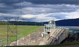 Lignes électriques avec un barrage à l'arrière-plan Photographie stock
