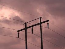 Lignes électriques contre un coucher du soleil orageux image stock