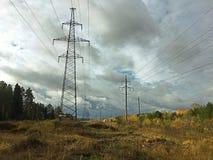 Lignes électriques dans la forêt sous les nuages image libre de droits