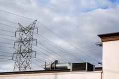 Lignes électriques des poteaux en métal au toit de construction contre un ciel nuageux gris photos libres de droits