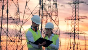 Lignes électriques et deux ingénieurs de spécialistes travaillant au développement d'énergie renouvelable pendant le coucher du s banque de vidéos