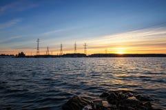 Lignes électriques sur les banques du réservoir au coucher du soleil Photo libre de droits