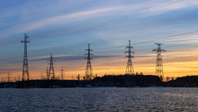 Lignes électriques sur les banques du réservoir au coucher du soleil Photo stock