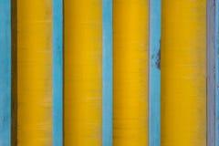 Lignes bleues verticales sur un fond jaune sale avec des ombres Texture de surface approximative photographie stock