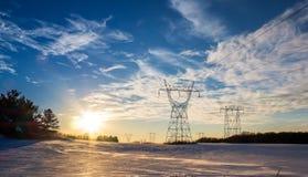 Lignes d'énergie hydraulique de transmission congelées par coucher du soleil de puissance élevée de neige d'hiver Images stock