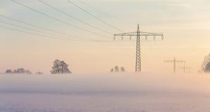 Lignes d'alimentation de brouillard et d'énergie pendant le lever de soleil pendant l'hiver Photographie stock libre de droits