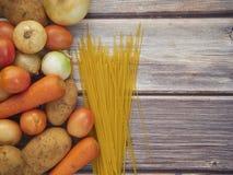 Lignes de légumes frais et de spaghetti sur de vieilles tables en bois photographie stock libre de droits