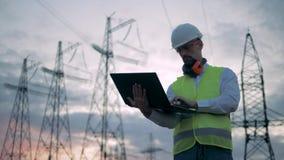 Lignes de transmission électriques et un inspecteur masculin travaillant près de eux banque de vidéos