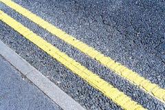 Lignes du trafic de stationnement interdit peintes double par jaune Photo libre de droits