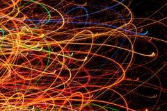 Lignes et courbes rougeoyantes multicolores lumineuses abstraites sur le fond noir Image libre de droits