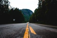 Lignes jaunes de route finissant à une montagne photographie stock libre de droits