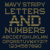 Lignes onduleuses d'or lettres et nombres Police rayée Photos stock