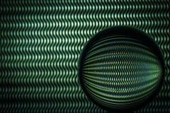 Lignes onduleuses vertes se reflétant dans une sphère en verre photo stock
