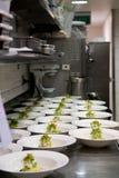 Lignes soignées de nourriture préparée dans une cuisine occupée Image libre de droits