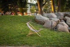 Ligstoel die zich op groen gras bij zonsondergang in Garnizon met rotsen, bomen en vage mensen op de achtergrond bevinden stock afbeelding