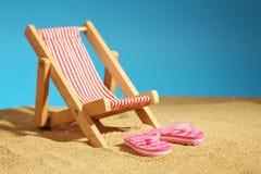 Ligstoel die zich op overzees zand en roze wipschakelaars met bloemen en blauwe hemel bevinden Royalty-vrije Stock Afbeelding