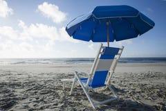 Ligstoel en Paraplu bij de Oceaan Stock Afbeelding