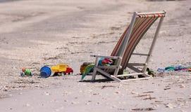 Ligstoel met speelgoed in strand Stock Afbeeldingen