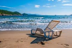 Ligstoel op een strand die uit op het overzees kijken Stock Foto
