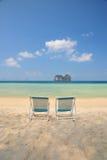 Ligstoel op wit zandstrand met glasheldere overzees Stock Foto's
