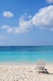 Ligstoel op zand met blauwe oceaan Stock Foto