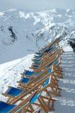 Ligstoelen die zich op piek in Alpen in de winter bevinden Stock Afbeeldingen