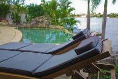 Ligstoelen door de pool Royalty-vrije Stock Afbeelding