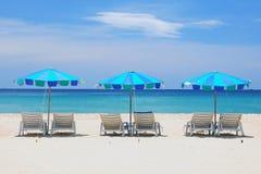 Ligstoelen en kleurrijke paraplu op het strand Stock Foto