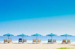 Ligstoelen en met paraplu op het strand Royalty-vrije Stock Afbeelding
