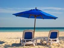 Ligstoelen en Paraplu door het Overzees stock afbeelding