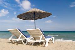 Ligstoelen en paraplu op tropisch strand Royalty-vrije Stock Afbeeldingen