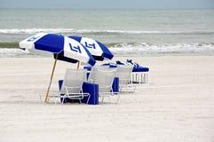 Ligstoelen en paraplu's Stock Afbeelding