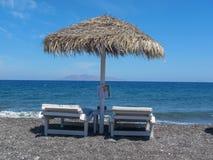 Ligstoelen en parasol bij kust Stock Afbeelding