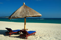 Ligstoelen en parasol door het overzees Stock Afbeelding