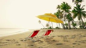 Ligstoelen en zonparaplu op het strand Zonsondergang op het eilandstrand stock video