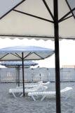Ligstoelen en zonparaplu's op het strand Stock Foto