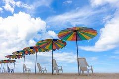Ligstoelen met kleurrijke paraplu bij het strand Stock Afbeelding