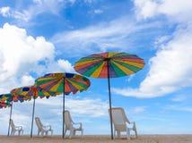 Ligstoelen met kleurrijke paraplu bij het strand Stock Foto