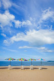 Ligstoelen met kleurrijke paraplu bij het strand Royalty-vrije Stock Afbeelding