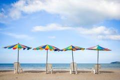 Ligstoelen met kleurrijke paraplu bij het strand Royalty-vrije Stock Afbeeldingen