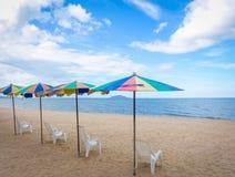 Ligstoelen met kleurrijke paraplu bij het strand Royalty-vrije Stock Fotografie